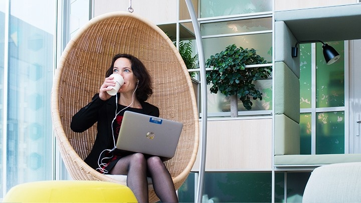 Woman holding her laptop and drinking coffee