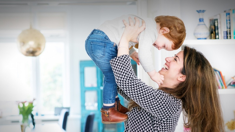 Woman lifting up her baby