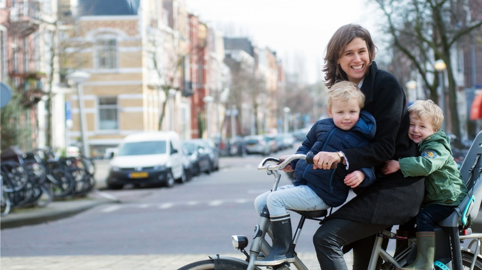 Woman on her bike and carrying two little boys