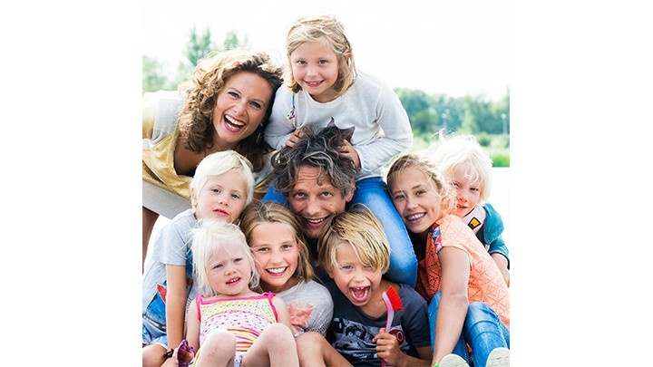 Man surrounded by his children and wife