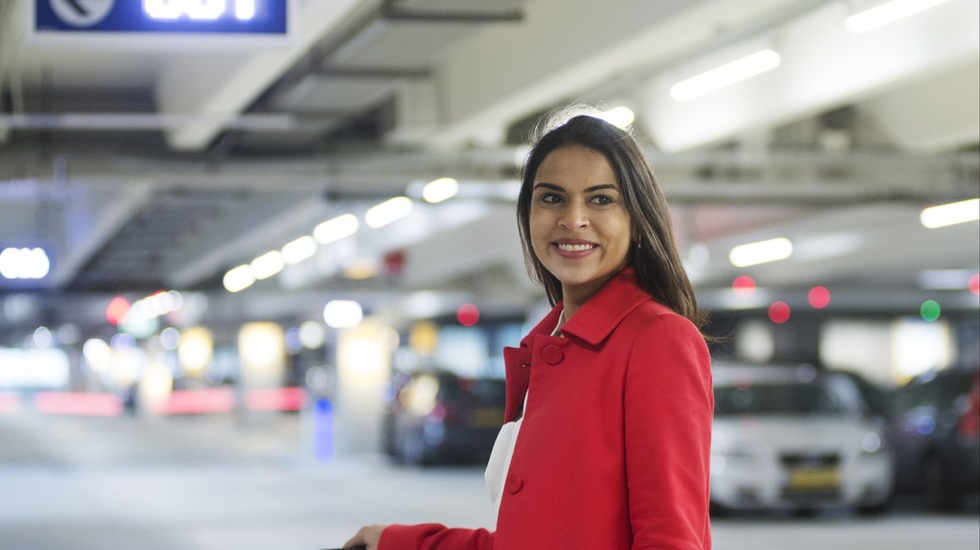 Woman in red coat smiling at a parking lot