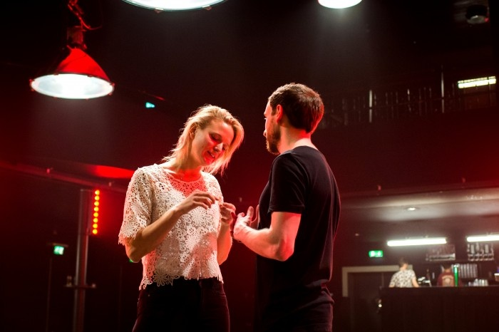 Blond woman and man in a dark room with red lights