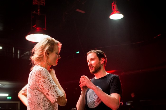 Blond woman listening to man in a dark room with red lights