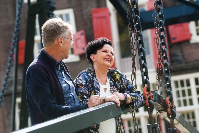 Older woman and older man hanging out in a bridge together