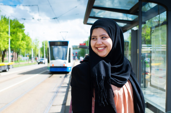 Women in hijab smiling in a tram stop