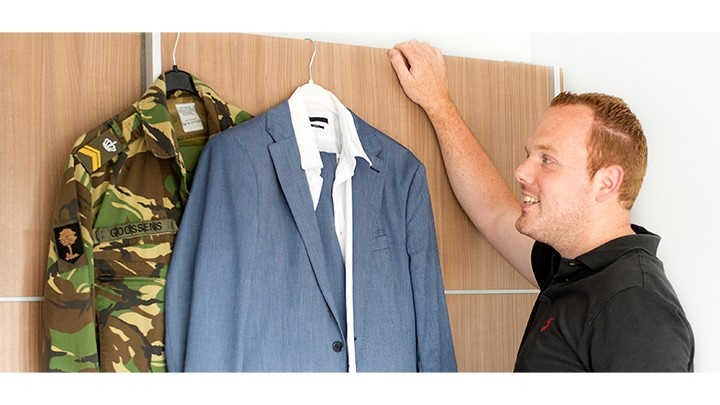 Man comparing his suit to his army uniform