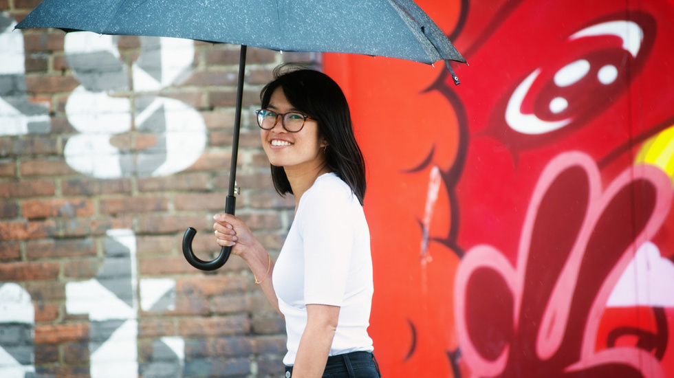 Women with glasses holding an umbrella and smiling