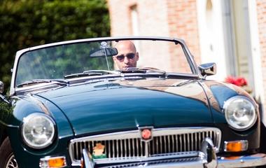 Bald man driving a retro car