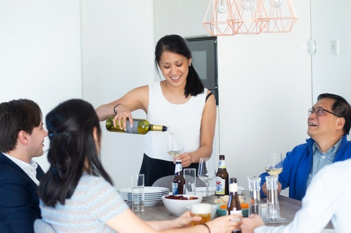 Asian woman pouring wine for a table of guests
