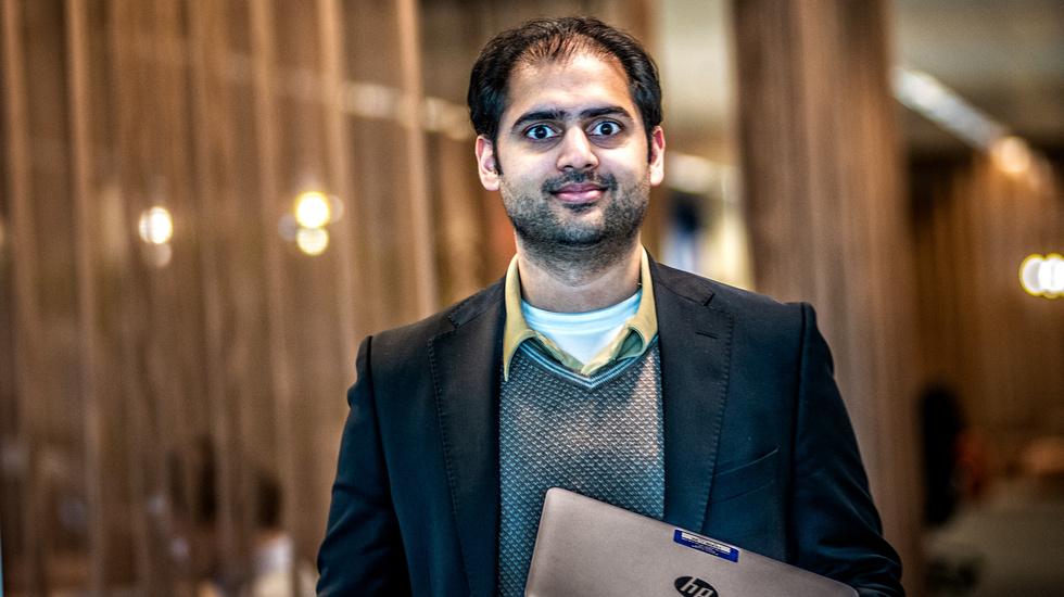 Indian man smiling at camera while holding laptop