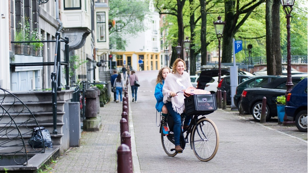 Woman biking with her daughter in her back