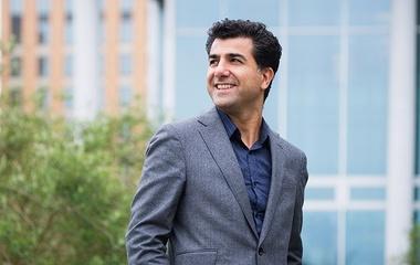 Man in grey suit looking left