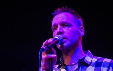 Man holding a mic under purple lighting