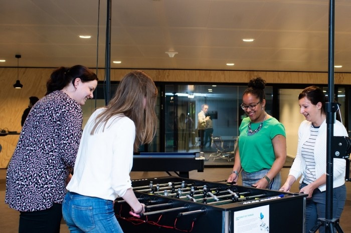 Four women playing foosball/ table soccer