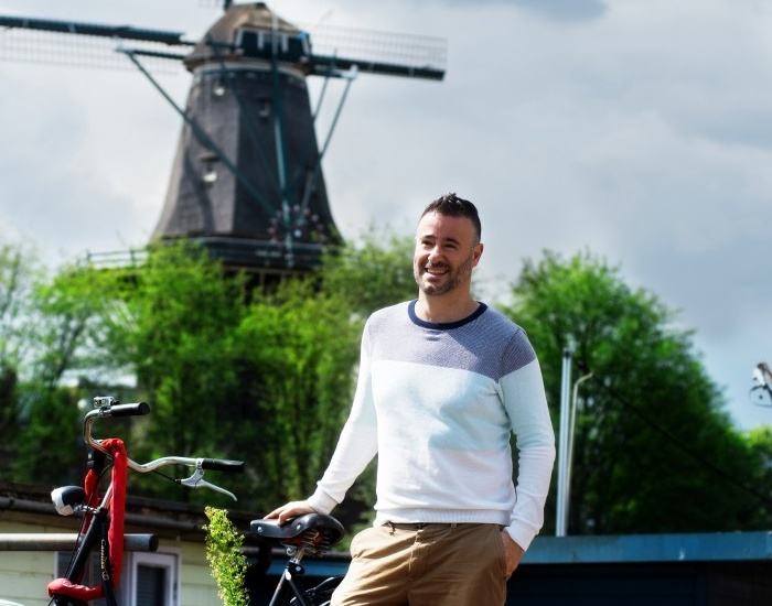 Man posing with his bicycle infront of a windmill