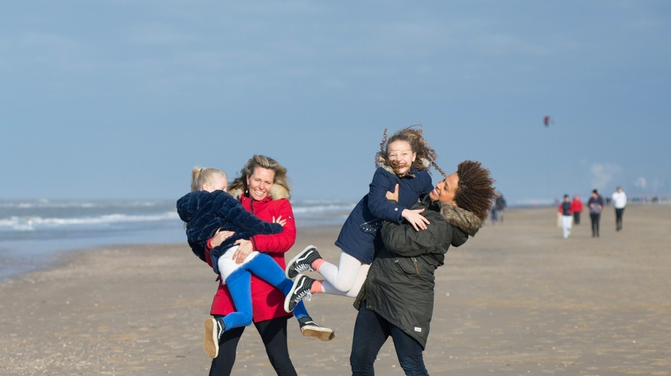 Two woman carrying their kids in the beach