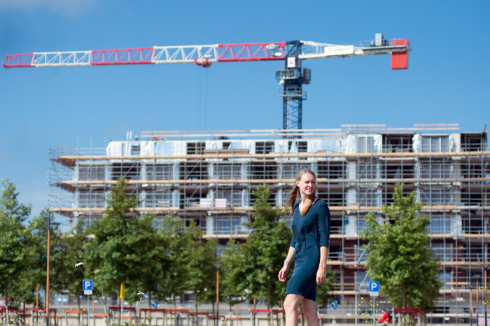 Women with blond hair posing infront of a building