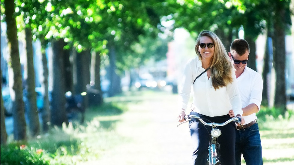 women biking while man holds her bike
