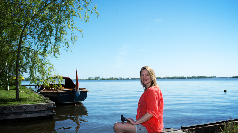 Woman sitting in the dock by the lake