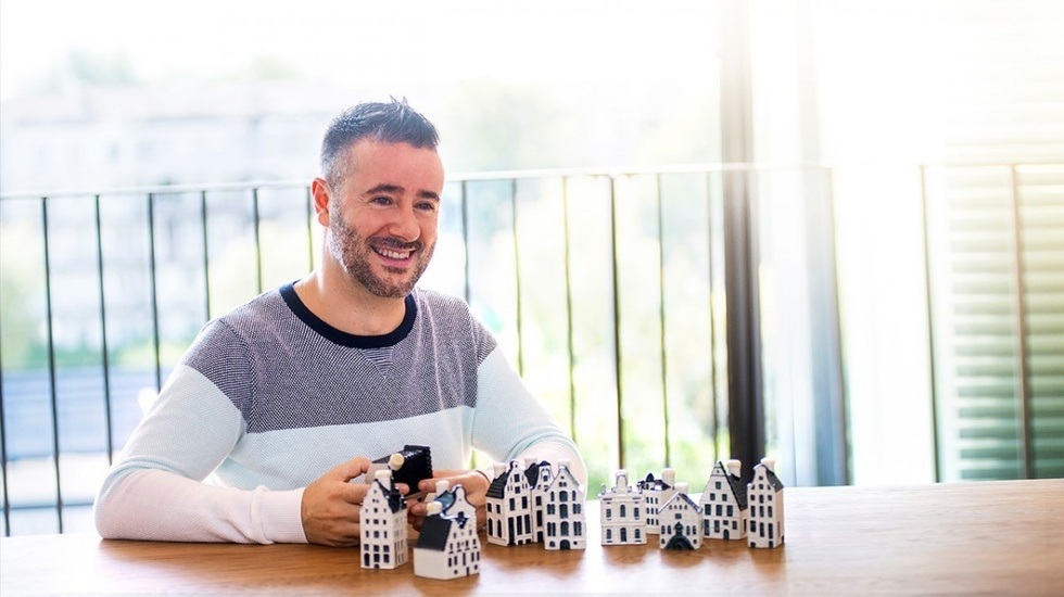 Man posing with small white houses