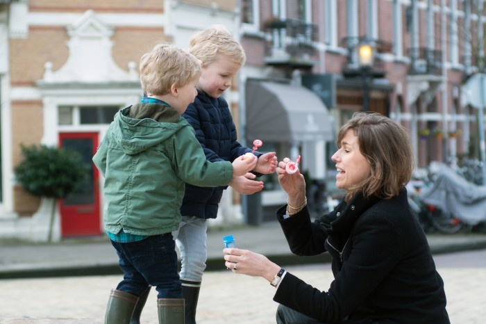 Woman and her two sons playing with bubbles
