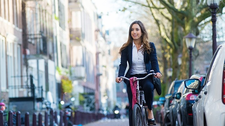 Woman dressed in a suit riding a bike