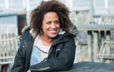 Woman with dark skin and curly hair wearing a winter jacket