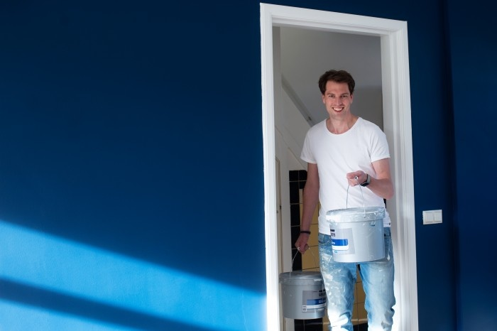 Man in a white shirt holding paint in a blue room