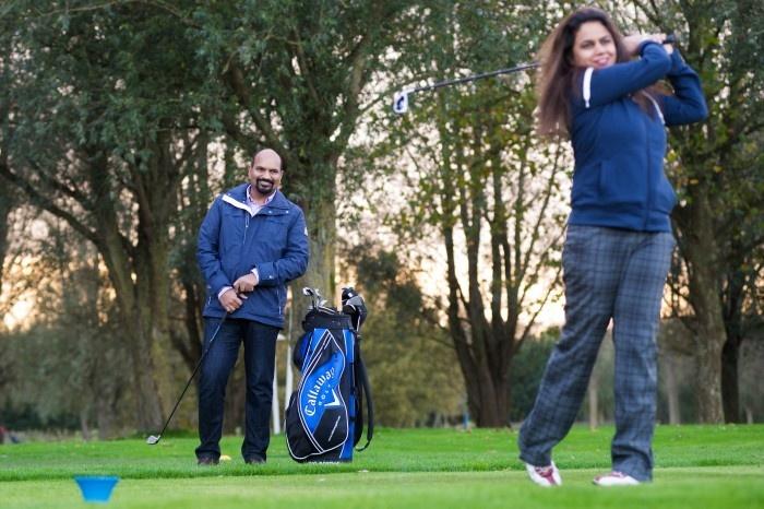 Man watching woman golfing