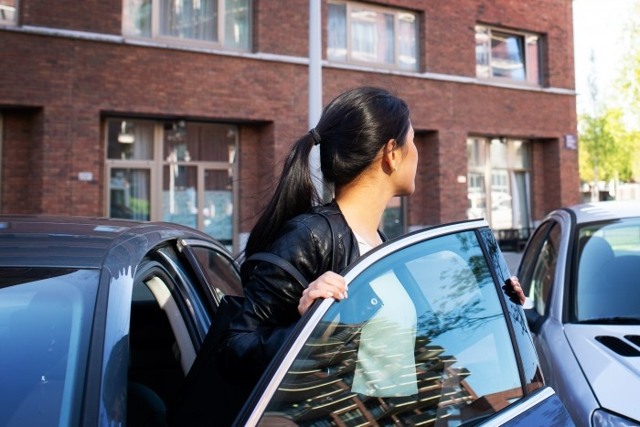 Asian woman going out of her car