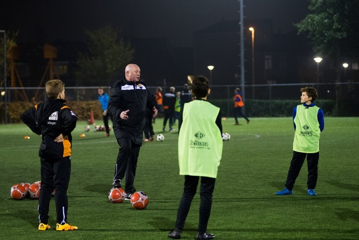 Bald man in a soccer firld coaching young boys