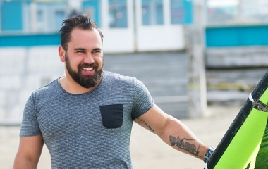 Smiling man with hand tattoo close up with Kitesurfing