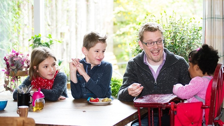 Man sitting around the dining table with his children