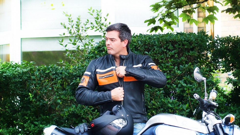 Man zipping up his jacket on a motorcycle