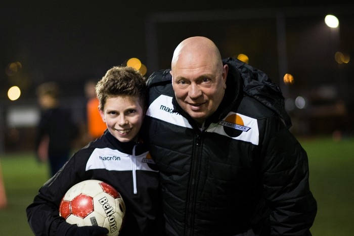 Bald man and young boy in a soccer field
