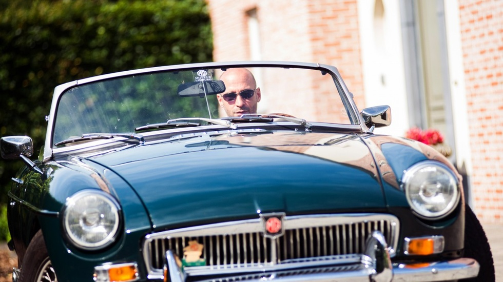 Bald man driving a retro car