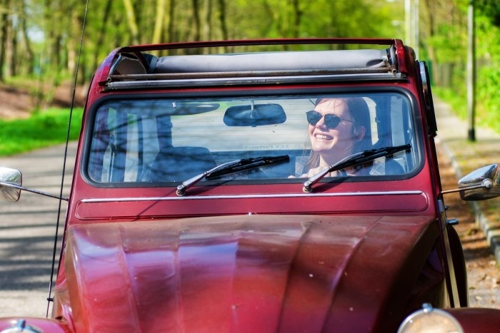 Woman wearing sun glasses and driving a red car