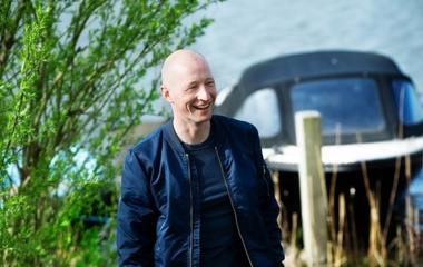 Bald man in dark blue bomber smiling