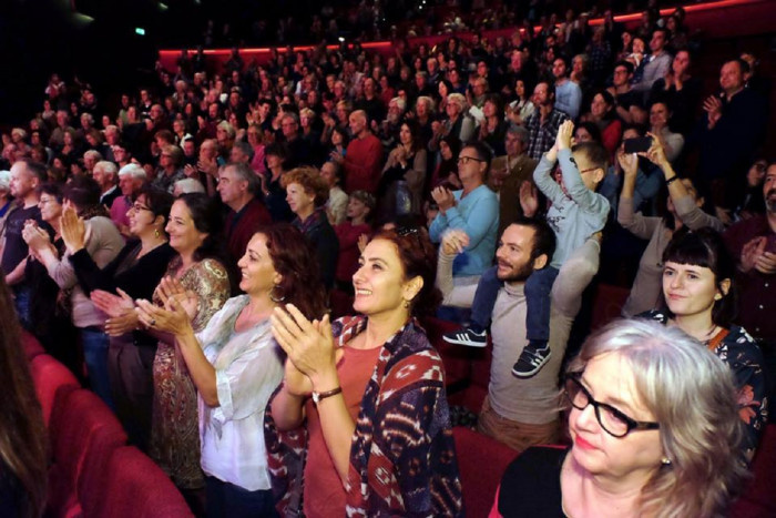 The audience standing and clapping