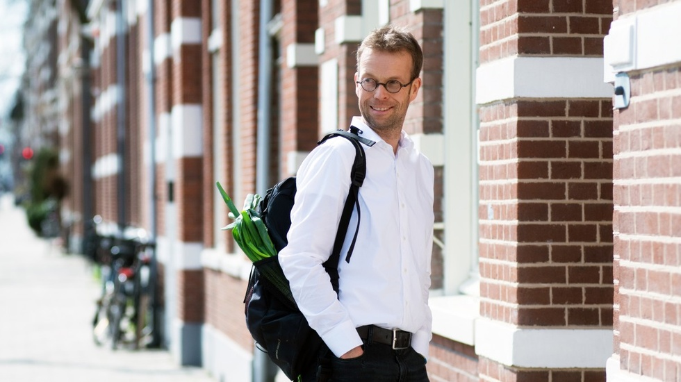 Man with glasses posing infront of a building