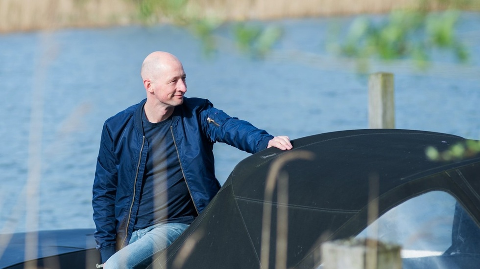 Bald man in dark blue bomber posing in from of a lake