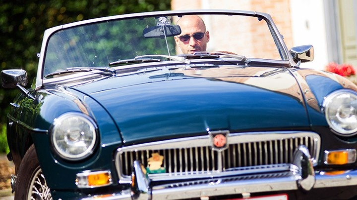 Bald man dirving a retro car close up