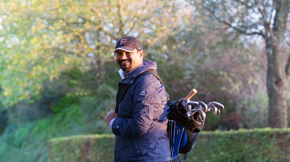 Man wearing a cap and carrying his golfbag