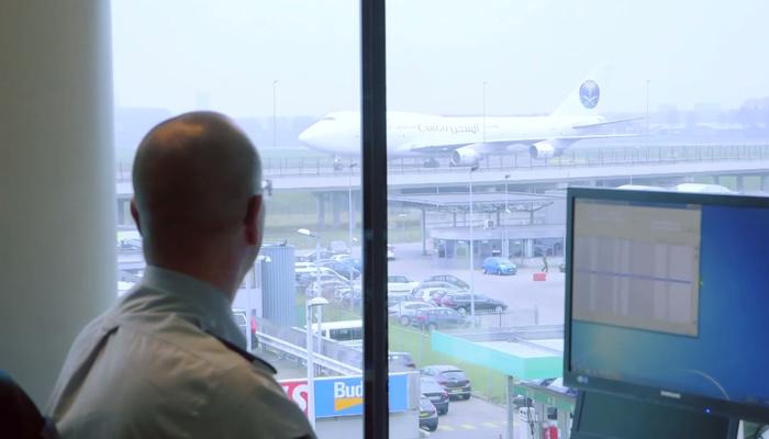 Een risico analyst kijkt uit het raam en houdt toezicht op een luchthaven.