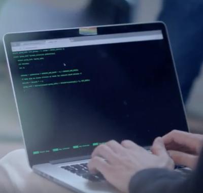 Man achter Laptop met groene letters