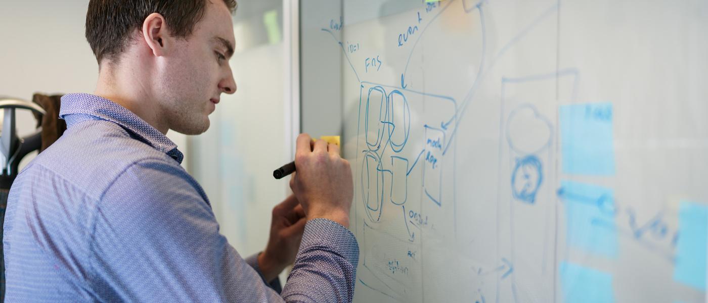 man schrijft iets op een whiteboard