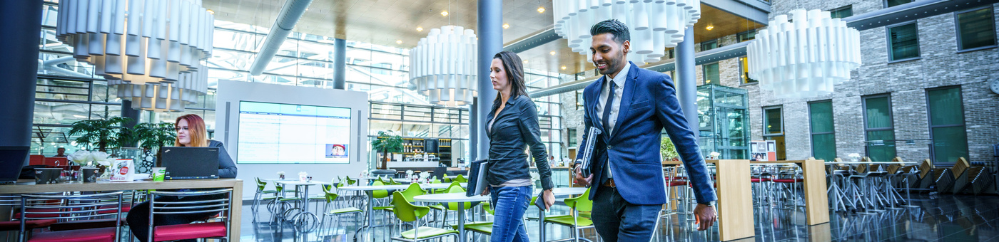 man en vrouw lopen door het restaurant gedeelte van een kantoor