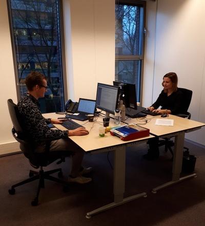 man en vrouw tegenover elkaar aan bureau