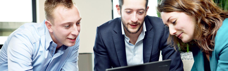 Trainees bekijken werk op laptop