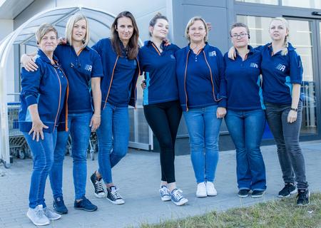 Grupa uśmiechniętych pracowników Action przed sklepem Action